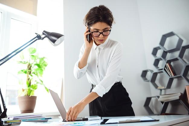 Jonge mooie zekere onderneemster die op telefoon op werkplaats in bureau spreekt.