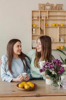 Jonge mooie zussen glimlachen naar elkaar