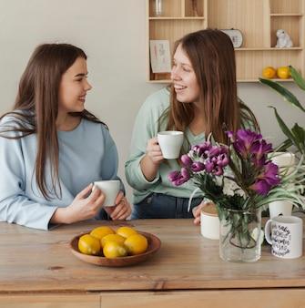 Jonge mooie zussen koffie drinken