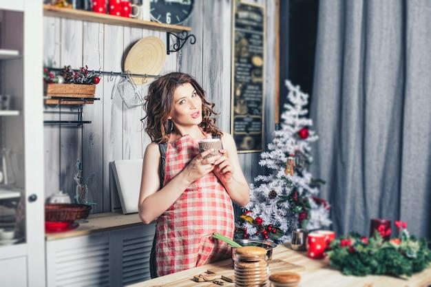 Jonge mooie zwangere met thuis in de keuken gelukkig lachend