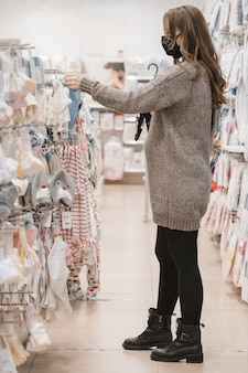 Jonge mooie zwangere vrouw in hygiënisch masker babykleding voor pasgeboren kiezen.