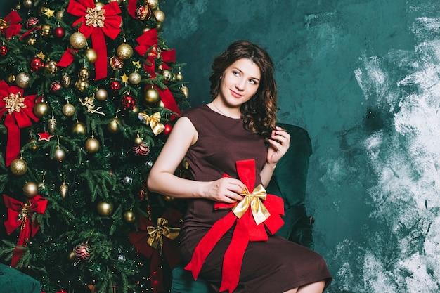 Jonge mooie zwangere vrouw in kerstmis met een mooie kerstboom versierd met