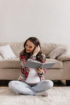 Jonge mooie zwangere vrouw in rood plaidoverhemd en denimbroek boek lezen en glimlachen