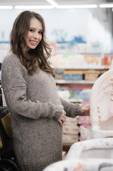 Jonge mooie zwangere vrouw kinderwagen of kinderwagen buggy voor pasgeboren kiezen.