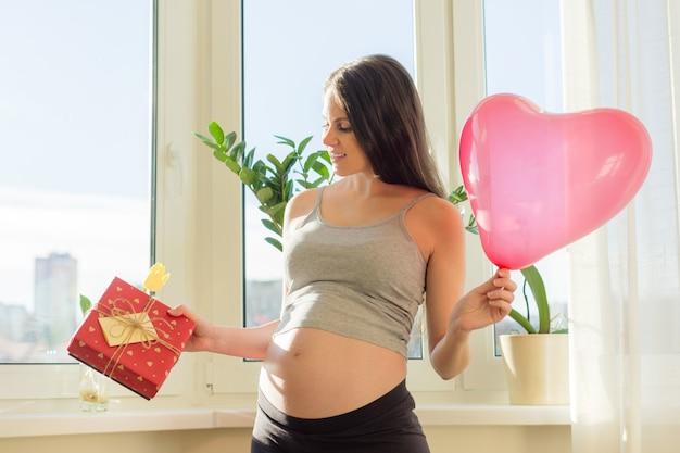 Jonge mooie zwangere vrouw met geschenkdoos en ballon hart