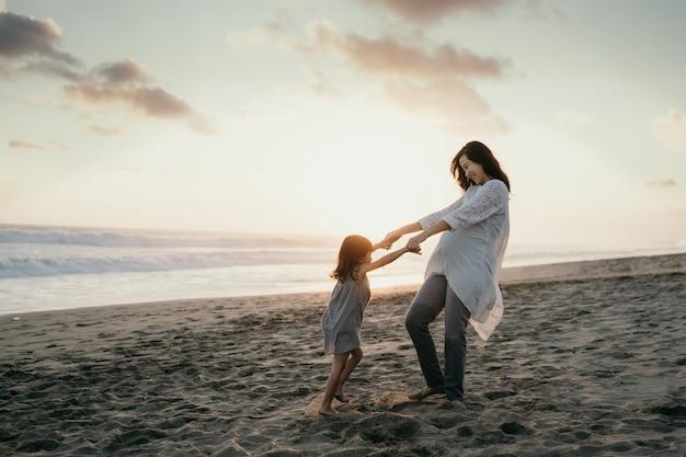Jonge mooie zwangere vrouw met haar kleine schattige dochter spelen in het strand