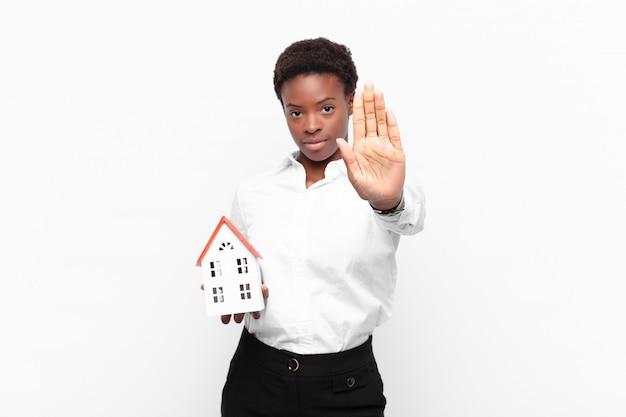 Jonge mooie zwarte die ernstig, streng, ontstemd en boos kijken die open palm tonen die eindegebaar met een huismodel maken