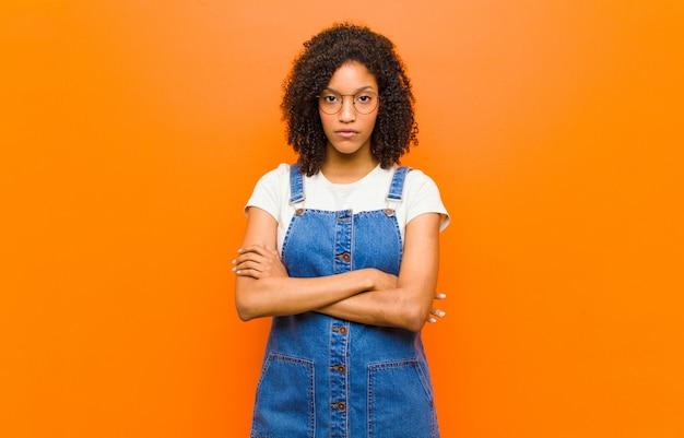Jonge mooie zwarte gevoel ontstemd en teleurgesteld, op zoek ernstig, geërgerd en boos met gekruiste armen tegen oranje muur