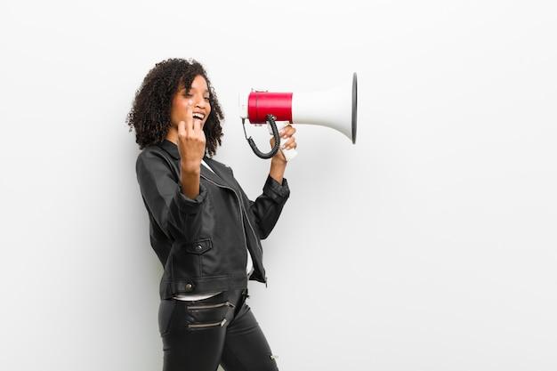 Jonge mooie zwarte met een megafoon die een leerjasje draagt tegen witte muur