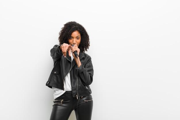 Jonge mooie zwarte met een microfoon die een leerjasje draagt tegen witte muur