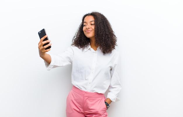 Jonge mooie zwarte met een slimme telefoon tegen witte muur