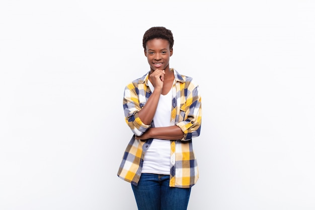 Jonge mooie zwarte vrouw die gelukkig kijkt en met hand op kin glimlacht, zich afvraagt of een vraag stelt, opties vergelijkt