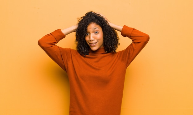 Jonge mooie zwarte vrouw die gelukkig, zorgeloos, vriendelijk en ontspannen genietend van het leven en succes, met een positieve houding ten opzichte van oranje muur