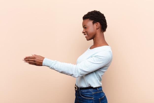 Jonge mooie zwarte vrouw die, u begroet en een handschok aanbiedt om een succesvolle overeenkomst, samenwerkingsconcept te sluiten