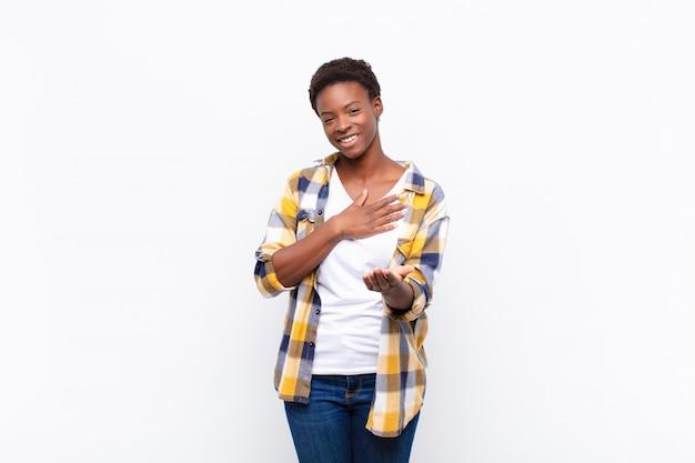 Jonge mooie zwarte vrouw die zich gelukkig en verliefd voelt, glimlachend met de ene hand naast het hart en de andere vooraan uitgestrekt