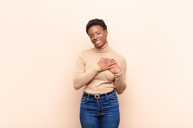 Jonge mooie zwarte vrouw gevoel romantisch, gelukkig en verliefd, vrolijk lachend en hand in hand dicht bij hart