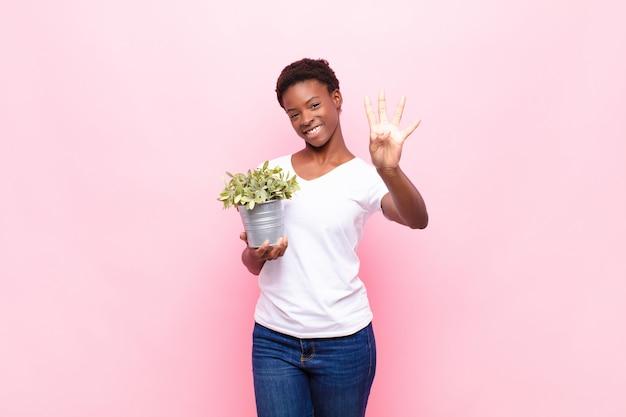 Jonge mooie zwarte vrouw glimlacht en kijkt vriendelijk, toont nummer vier of vierde met de hand naar voren, aftellend terwijl ze een plant vasthoudt