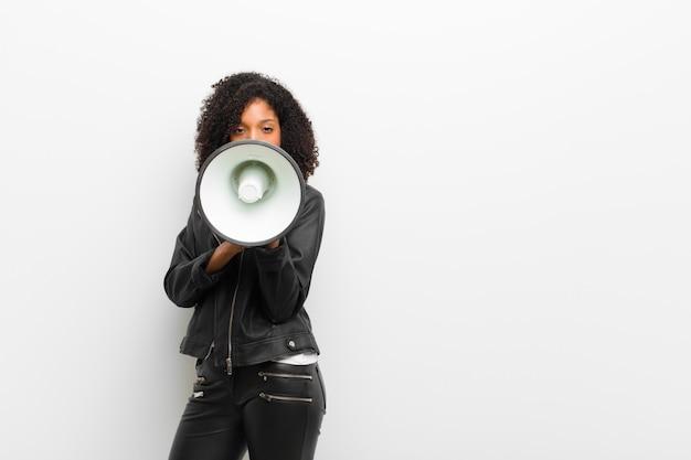 Jonge mooie zwarte vrouw met een megafoon die een leren jas draagt
