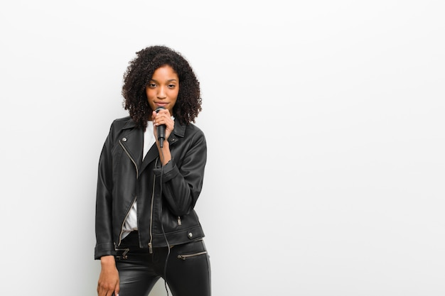 Jonge mooie zwarte vrouw met een microfoon die een leerjasje op witte muur draagt