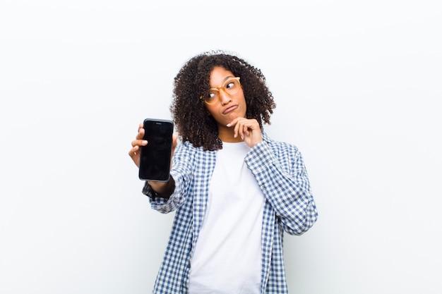 Jonge mooie zwarte vrouw met een slimme telefoon