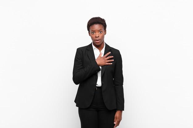 Jonge mooie zwarte vrouw voelen geschokt en verrast, glimlachend, hand in hart en nieren, blij om de ware te zijn of dankbaarheid te tonen tegen de witte muur