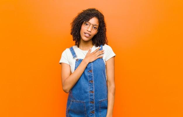 Jonge mooie zwarte vrouw voelt zich geschokt en verrast, glimlachend, hand in hart en nieren, blij om de ware te zijn of dankbaarheid te tonen over de oranje muur