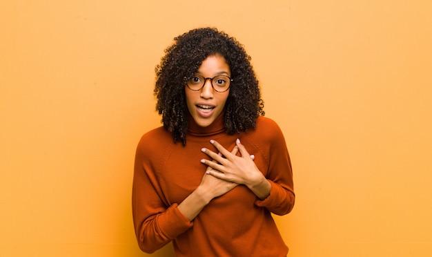 Jonge mooie zwarte vrouw voelt zich geschokt en verrast, glimlachend, hand in hart en nieren, blij om de ware te zijn of dankbaarheid te tonen tegen de oranje muur