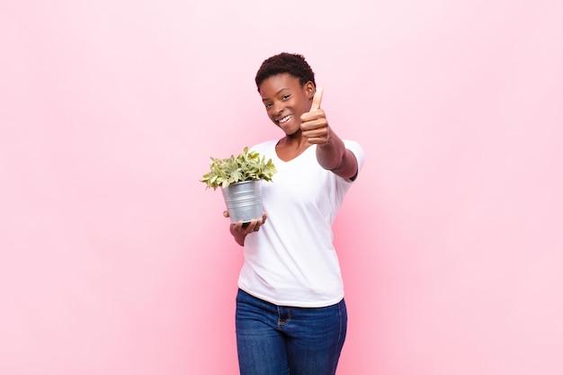 Jonge mooie zwarte vrouw voelt zich trots, zorgeloos, zelfverzekerd en gelukkig, glimlachend positief met duimen omhoog houden van een plant