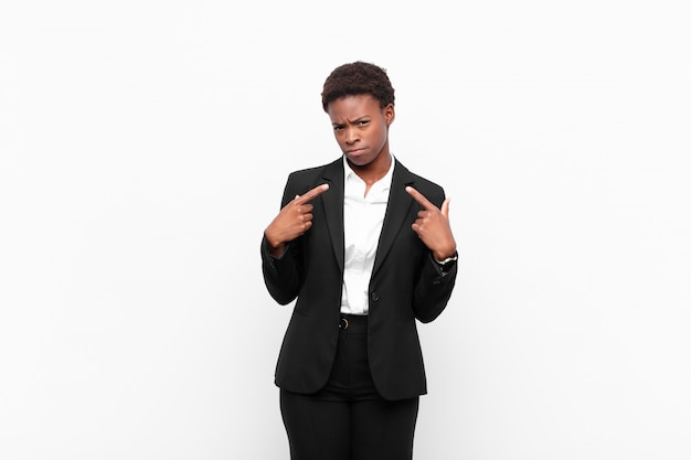 Jonge mooie zwarte womanwith een slechte houding die trots en agressief kijkt, naar omhoog richt of pretbord met handen tegen witte muur maakt