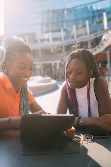 Jonge mooie zwarte zusters buitenverlichting met behulp van tablet