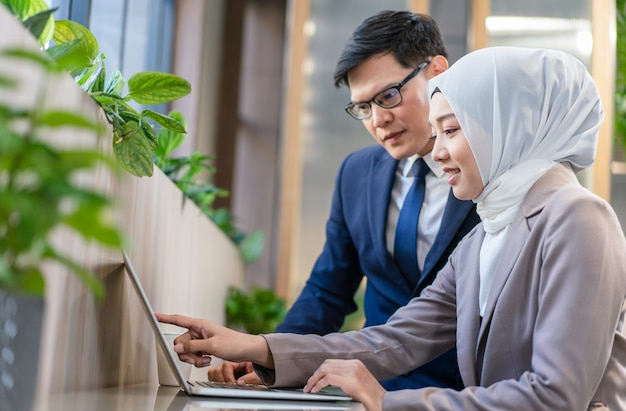 Jonge moslim zakenvrouw met zakenman samen kijken naar laptop tijdens het werken op de werkplek
