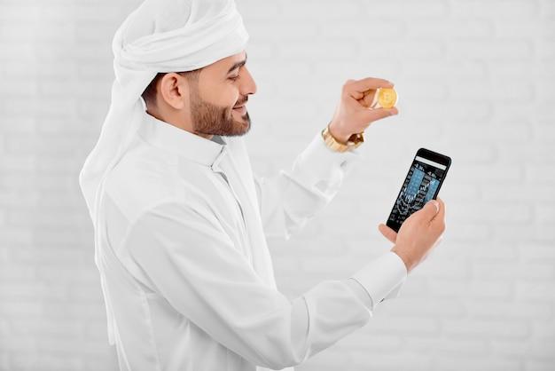 Jonge moslimhandelaar houdt gouden bitcoin en mobiele telefoon