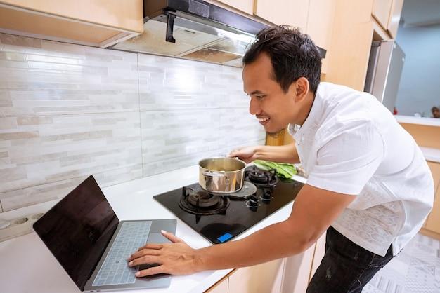Jonge moslimmannetje thuis koken door tutorial op internet te kijken met zijn laptop in de keuken