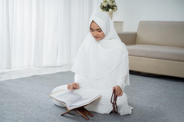 Jonge moslimvrouw bidden in witte traditionele kleding