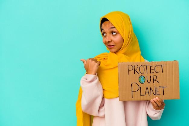 Jonge moslimvrouw die beschermt onze planeet op blauwe punten met duimvinger weg, lachend en zorgeloos houdt.