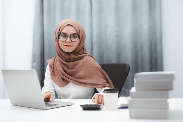 Jonge moslimvrouw die bruine hijab draagt die met laptop in haar huis werkt.