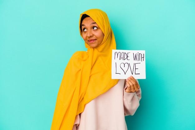 Jonge moslimvrouw die een gemaakt met liefdeaanplakbiljet houdt dat op blauwe muur wordt geïsoleerd die droomt van het bereiken van doelstellingen en doeleinden