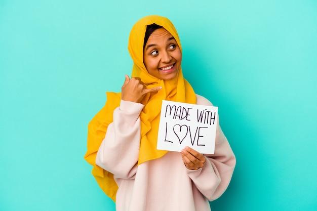 Jonge moslimvrouw die een gemaakt met liefdeaanplakbiljet houdt dat op blauwe muur wordt geïsoleerd die een mobiel telefoongesprekgebaar met vingers toont.