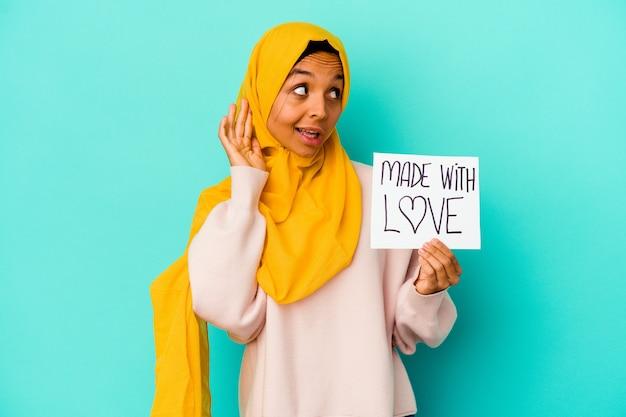 Jonge moslimvrouw die een gemaakt met liefdeaanplakbiljet op blauw houdt dat probeert om een roddel te luisteren.