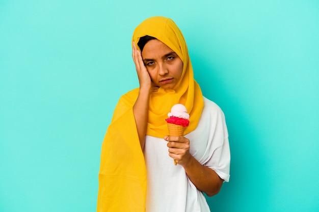 Jonge moslimvrouw die een ijsje eet dat op een blauwe achtergrond wordt geïsoleerd en geschokt is, herinnert zich een belangrijke vergadering.
