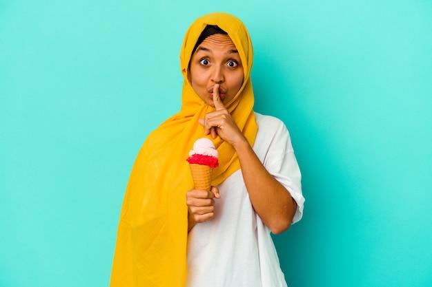 Jonge moslimvrouw die een ijsje op blauw eet dat een geheim houdt of om stilte vraagt.