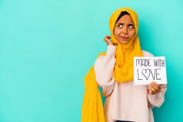 Jonge moslimvrouw die een plakkaat gemaakt met liefde houdt dat op blauwe muur wordt geïsoleerd die achterkant van het hoofd raakt, denkt en een keuze maakt