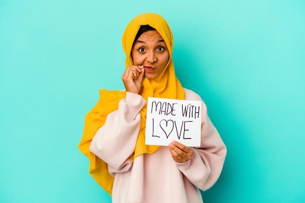 Jonge moslimvrouw die een plakkaat gemaakt met liefde op blauw met vingers op lippen houdt die een geheim houden.