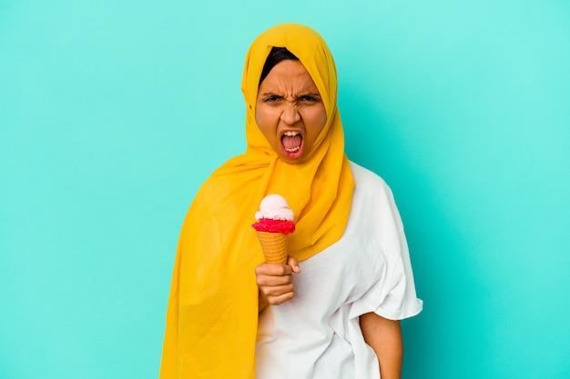Jonge moslimvrouw die een roomijs eet dat op blauwe muur wordt geïsoleerd die zeer boos en agressief gilt