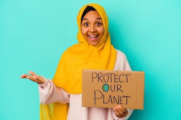 Jonge moslimvrouw die houdt beschermt onze planeet geïsoleerd op blauwe muur die een aangename verrassing ontvangt, opgewonden en handen opheft