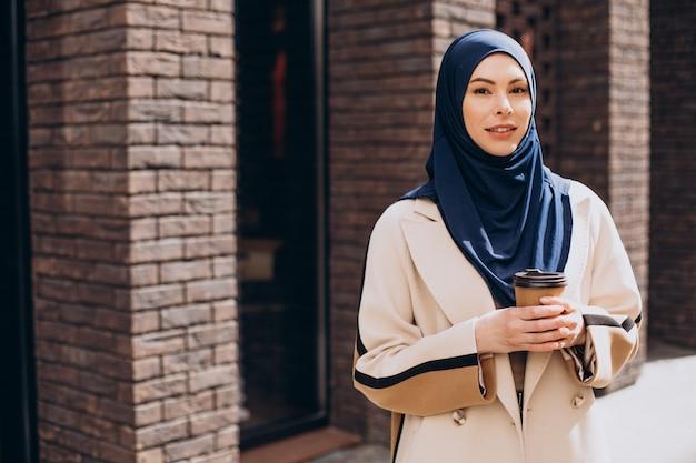 Jonge moslimvrouw die koffie drinkt