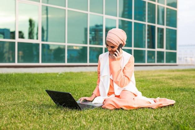 Jonge moslimvrouw die mobiele telefoon en laptop in park met behulp van