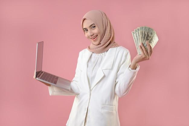 Jonge moslimvrouw die online aan laptop werkt en geld houdt