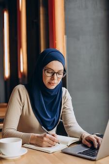 Jonge moslimvrouw die online werkt op de computer in een café