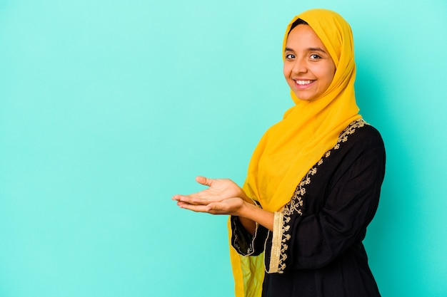 Jonge moslimvrouw die op blauw een exemplaarruimte op een palm houdt.